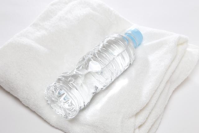 水の入ったペットボトルとバスタオル