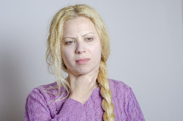 喉をおさえる女性