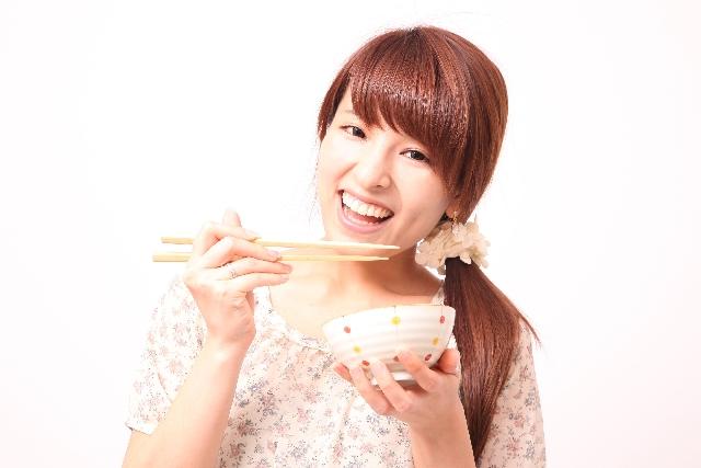 箸と茶碗を持つ笑顔の女性