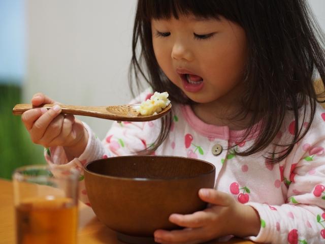 パジャマでご飯を食べる少女