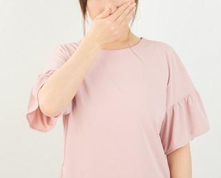鼻と口を押さえる女性